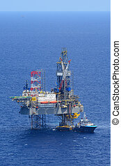The offshore drilling oil rig and supply boat side view