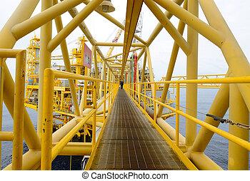 the worker is walking cross the pathway bridge of offshore oil rig