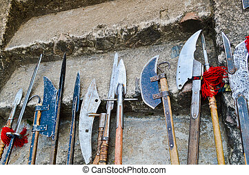 The old ancient medieval cold weapons, axes, olibards, knives, swords with wooden handles lick on the stone steps of the castle
