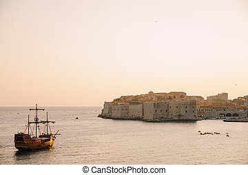The old city of Dubrovnik against the sunset sky. The wooden sailing ship Galleon approaches the main pier of Dubrovnik.