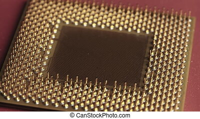 The old computer processor spins on a red background. CPU. Gold plated contacts of the microprocessor. Close-up. Chip processor computer. Central processor unit pins. Old model. Macro. Microchip