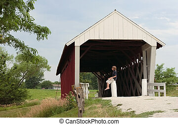 The Old Covered Bridge - A teenager sits on a post by a...