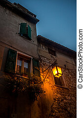 The old facade of a house with shutters and street light in small italian town