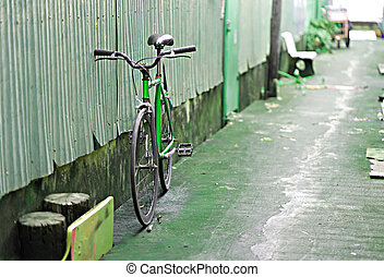 The old green bicycle parked against the wall.