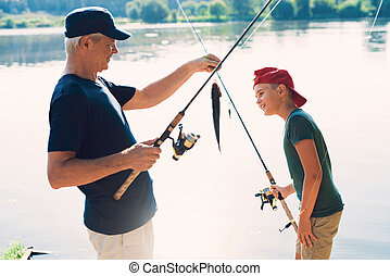 The old man and the boy are standing on the river bank with spinning arms. The old man shows the boy the fish he caught