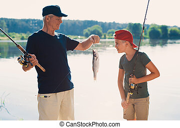 The old man boasts to the grandson of the fish he just caught in the river by spinning