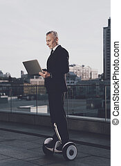 The old man is riding a gyroboard and is holding an open laptop in his hands. He has a strict business suit