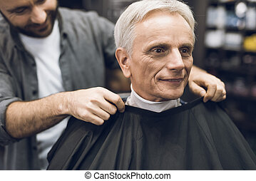 The old man is sitting in the barber's chair in a man's barbershop, where he came to cut his hair.