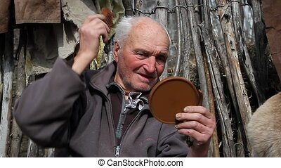 The old man sits on a stump on a farm with a mirror in his...