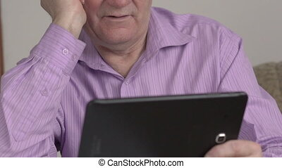 The old man uses tablet. Close-up