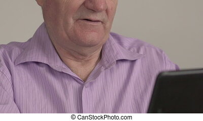The old man uses tablet, smile. Slowly