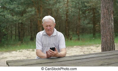 The old man uses the phone at the table in the forest