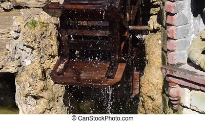 The old mill wheel - The mill wheel rotates under a stream...