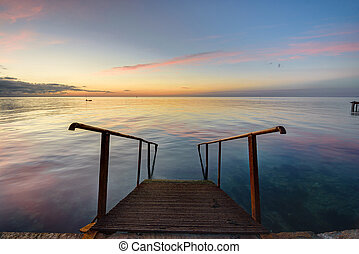 The old mittal staircase on the pier descends into the sea, against the background of the evening beautiful sunset