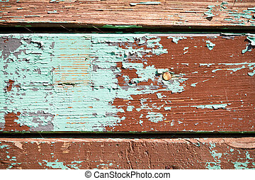 The old planks with peeling multicolor paint
