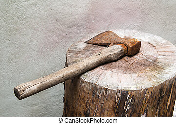The old rusty axe lays on a log