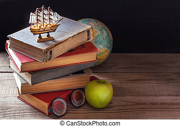 The old school books, textbooks and school supplies lie on a wooden table. Globe in the background.