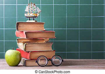 The old school books, textbooks and school supplies lie on a wooden table.