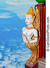 The Old sculpture of deva isolated on blue sky background