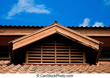 The Old tile of roof on blue sky background