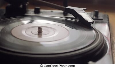 The old vintage gramophone reproduces the track. Close up...