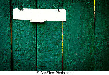 The old vintage wooden fence with metal sign