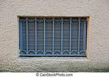 The old window with a gray iron grill on a brown concrete wall