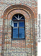 The old window with an open window on a brick wall