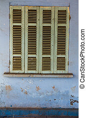 The old window with blue closed shutters on an old house. Vintag