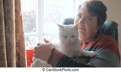 The old woman caress cat sitting at a window. Smiling aged...