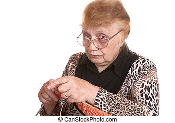 The old woman is engaged in knittin