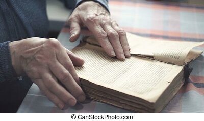 the old woman leafs through and reads an old antique book