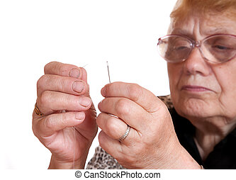The old woman passes thread in needle