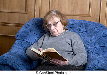 The old woman sits in an armchair