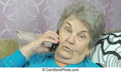 The old woman talking on a mobile phone at home