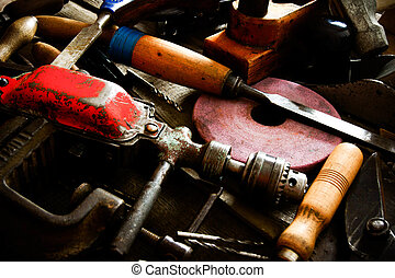 The old working tool. Many old working tools ( ruler, drill, chisel and others) on a wooden background.