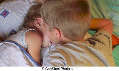 the older brother gently kissed the sleeping younger brother at home