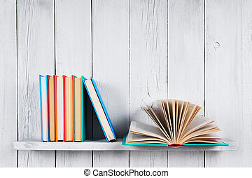 The open book and other multi-coloured books. On a wooden shelf. A wooden, white background.