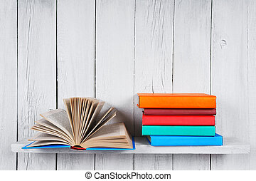 The open book and other multi-coloured books. On a wooden...