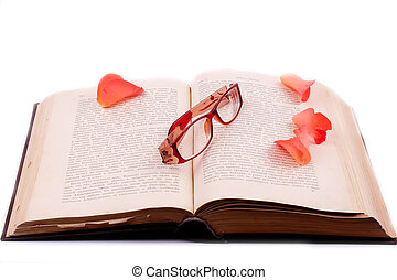 The open book with glasses and rose petals