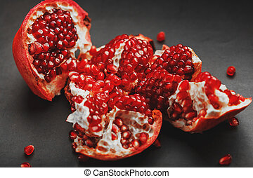 The opened Fruits of a ripe open pomegranate lie on a black textural background.