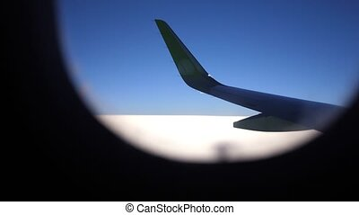 The opening of the porthole and the view of the wing of the aircraft in the sky. slow motion.