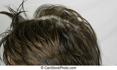 The overgrown gray roots of a middle-aged woman who colouring her hair herself with special brush. Dark hair and white roots of a woman's head on a white background. Hair care in salon close up view