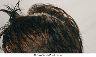 The overgrown gray roots of a middle-aged woman who colouring her hair herself with special brush. Dark hair and white roots of a woman's head on a white background. Hair care in salon close up view.