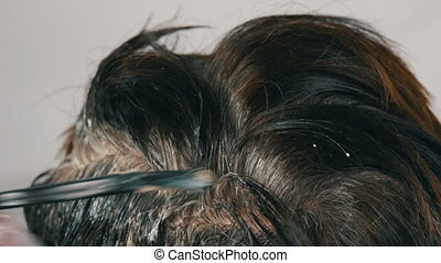 The overgrown gray roots of a middle-aged woman who dues her...