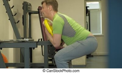 A mature overweight man in a green T-shirt does squats with a weight for a barbell. Fitness training. Healthy lifestyle concept