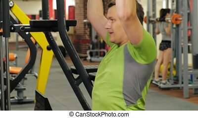 The overweight man shares the upper block in the gym....