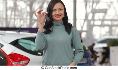 The owner shows the thumbs up. Auto business, car sale, dealership, rental, technology and people concept. Vehicle, rental, automotive concept. Commercial exhibition and rental vehicle concept. Young woman in a motor show. Woman buying the car. Young woman consultant in show room standing near car. ...