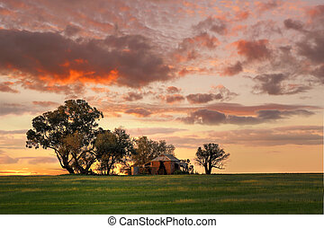 Australian outback sunset. Old farm house, crumbling walls and verandah with two water tanks out back sits abandoned on a hill at sunset. The last sun rays stretching across the landscape painting the grass in dappled light and edging the tanks and house in warm glow.