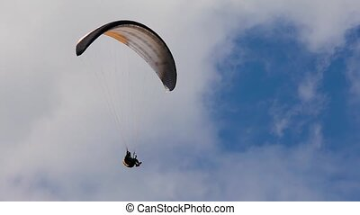 The paraglider in the sky, flies in the air streams. The...